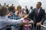 Barack Obama (d) salue des sympathisants à son arrivée à l'aéroport de Charlotte, le 5 septembre 2012