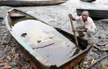Un habitant de Bodo essaie de séparer le pétrole de l'eau dans un bateau, le 11 août 2011 au Nigeria