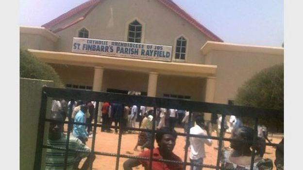 Des fidèles devant une église touchée par un attentat à Jos le 11 mars 2012, au Nigeria