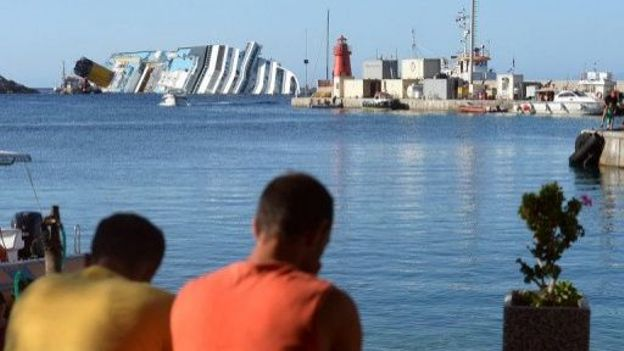 Des touristes regardent l'épave du Costa Concordia, le 13 juillet 2012 sur l'île du Giglio