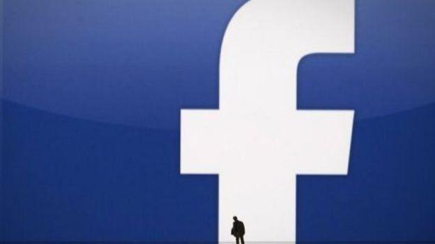 Une silhouette devant le logo Facebook