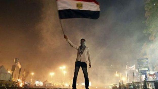 Un Egyptien agite un drapeau national place Tahrir au Caire lors d'une manifestation contre le pouvoir islamiste, le 25 janvier 2013